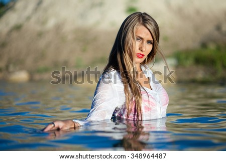 Caucasian long hair model posing in wet white shirt in water. - stock photo