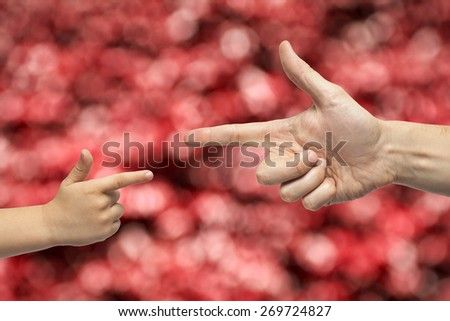 Caucasian male and boy hands pointing, or gun gesture, on blurred red background. - stock photo