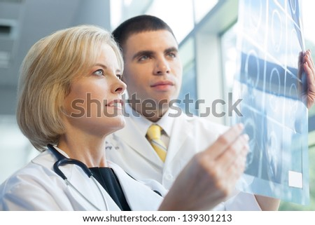 Caucasian male and female doctors in white lab coats looking at an x-ray in brightly lit  hospital.. - stock photo