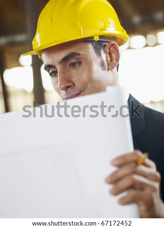 caucasian male architect examining blueprint. Vertical shape, waist up, side view, copy space - stock photo