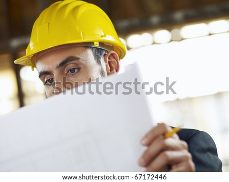 caucasian male architect examining blueprints. Horizontal shape, head and shoulders, front view, copy space - stock photo