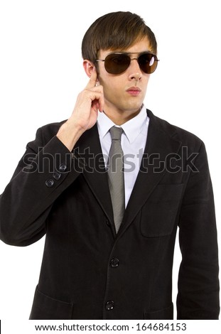 Caucasian male bodyguard wearing sunglasses and black suit - stock photo