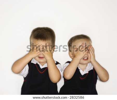 Caucasian male children twins with hands over eyes. - stock photo