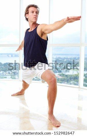 Caucasian male doing yoga warrior pose indoors in high rise apartment - stock photo