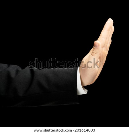 Caucasian male hand in a business suit, opened palm stop gesture sign, low-key lighting composition, isolated over the black background - stock photo