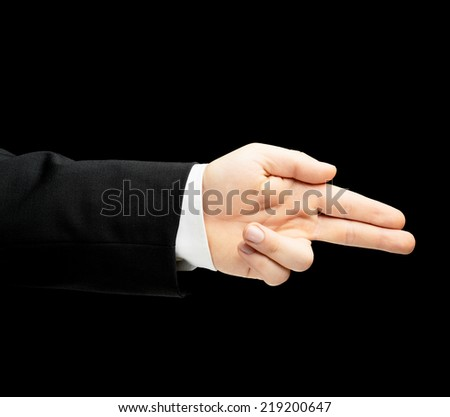 Caucasian male hand in a business suit, pointing gun gesture sign, low-key lighting composition, isolated over the black background - stock photo