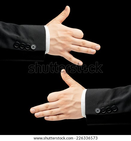 Caucasian male hand in a business suit, showing a dog gesture sign, low-key lighting composition, isolated over the black background - stock photo