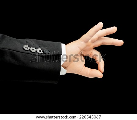 Caucasian male hand in a business suit, showing an approval okay gesture sign, low-key lighting composition, isolated over the black background - stock photo