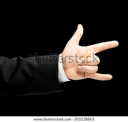 Caucasian male hand in a business suit, showing the sign of horn gesture, low-key lighting composition, isolated over the black background - stock photo