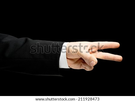 Caucasian male hand in a business suit, showing the two fingers victory gesture sign, low-key lighting composition, isolated over the black background - stock photo
