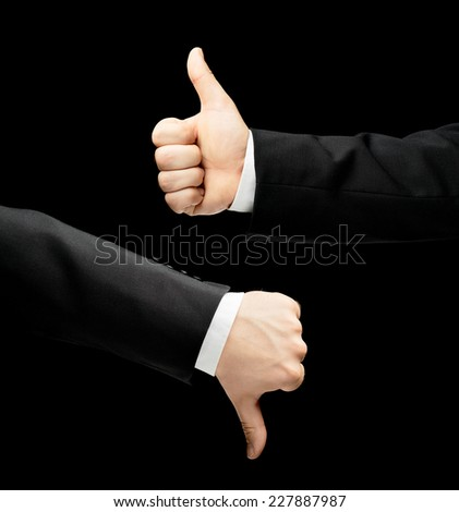 Caucasian male hand in a business suit, showing thumbs up and down gesture signs, low-key lighting composition, isolated over the black background - stock photo