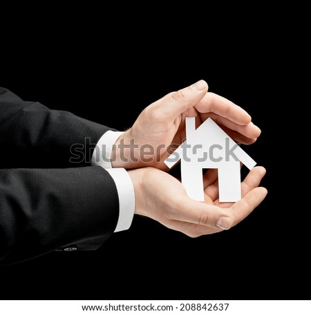 Caucasian male hands in a business suit, holding the paper cut house shape in both palms, low-key lighting composition, isolated over the black background - stock photo