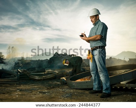 caucasian male inspector standing on construction site, taking notes, with man welding metal in background. copy space available - stock photo