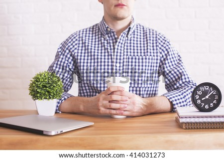 Caucasian male with coffee cup in hands sitting at wooden desk with closed laptop, plant and clock. White brick wall in the background - stock photo