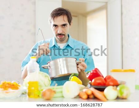 caucasian man eats from pan at home - stock photo