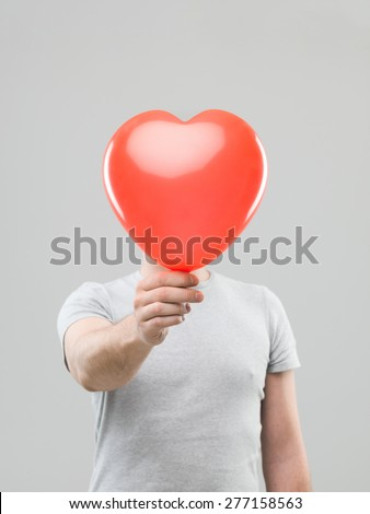 caucasian man holding heart shaped ballon in front of his head, against grey background - stock photo