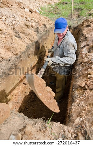 Caucasian man in blue cap digs grave at cemetery - stock photo