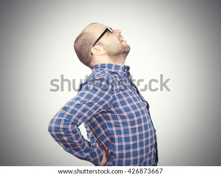 Caucasian man in blue shirt struggles with intense back pain on white background.      - stock photo