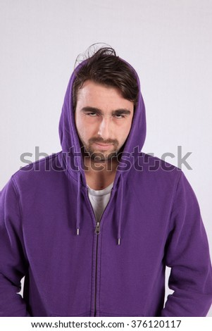Caucasian man in purple sweatshirt with a hood , looking thoughtful and mysterious - stock photo