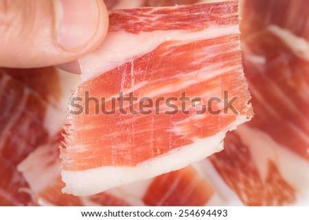 Caucasian man left hand taking serrano ham slice, top view - stock photo