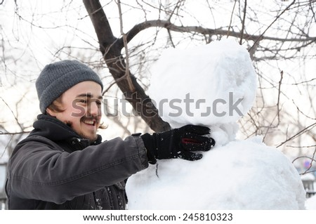 Caucasian man making snowman with snow outdoor - stock photo