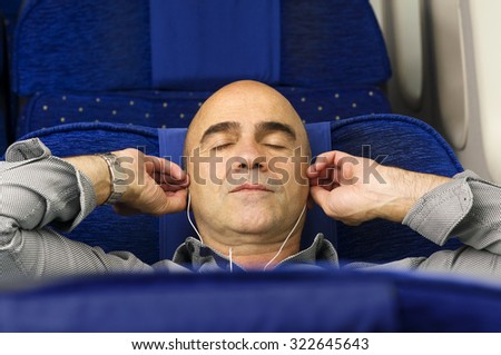 caucasian man passenger in airplane  resting in the seat  using mobile smart device with  headphones in comfortable flight and trip  - stock photo