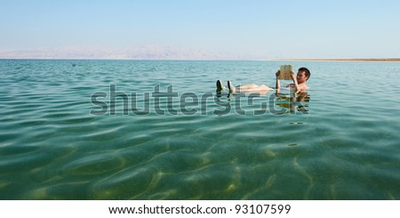 Caucasian man reads a book floating in the waters of the Dead Sea in Israel - stock photo
