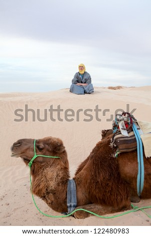 Caucasian man sitting on sand dune in desert with camel on foreground - stock photo