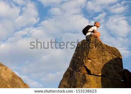 Caucasian man sitting on the mountain top after a successful hiking expedition in summer - stock photo