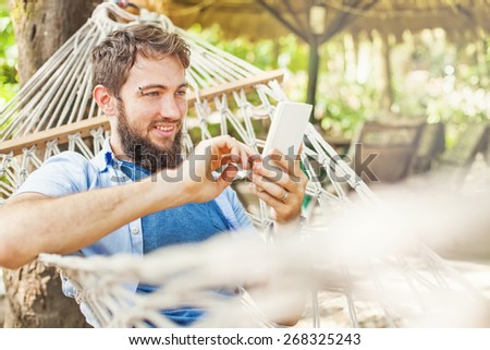 caucasian man using an app on his mobile phone white swinging in a hammock - stock photo