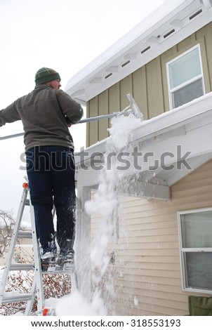 Caucasian man using rake to shovel heavy snow off roof - stock photo
