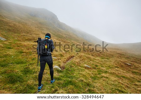 Caucasian man with backpack hiking into the mountains - stock photo