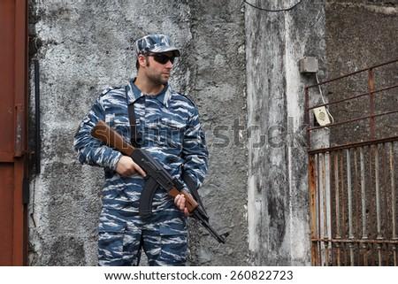 Caucasian man with black sunglasses in urban warfare holding weapon near grade. Selective focus - stock photo