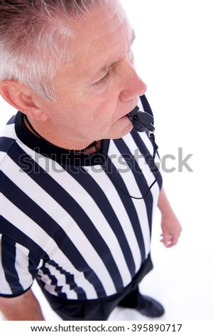 Caucasian man with referee uniform and a black whistle in his mouth shot in a vertical format at an angle - stock photo
