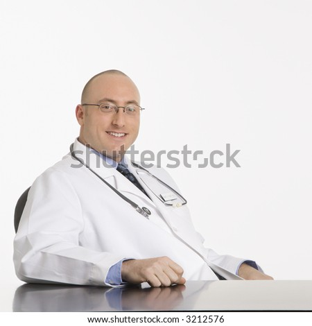 Caucasian mid adult male physician sitting at desk smiling. - stock photo