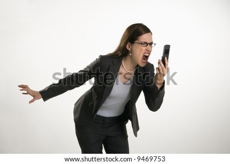 Caucasian mid adult professional business woman yelling into cell phone in anger. - stock photo