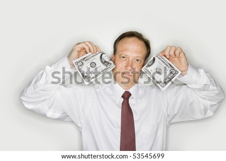 Caucasian middle aged businessman holding hudred dollar bill ripped in half. - stock photo