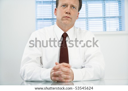 Caucasian middle aged businessman sitting at desk in meditation. - stock photo
