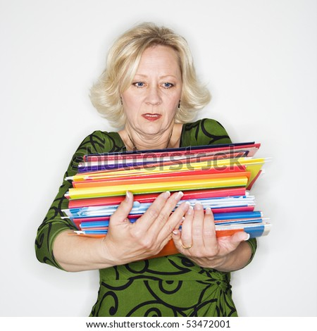 Caucasian middle aged businesswoman carrying stack of folders. - stock photo