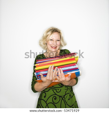 Caucasian middle aged businesswoman carrying stack of folders smiling. - stock photo
