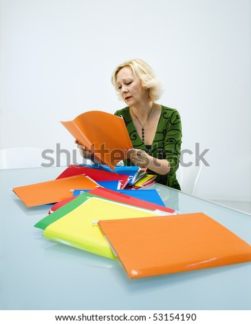 Caucasian middle aged businesswoman sitting at office desk going through pile of folders. - stock photo