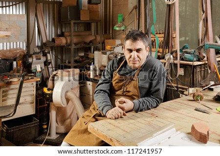 Caucasian middle-aged craftsman sitting in his workshop at workbench and looking sideways - stock photo