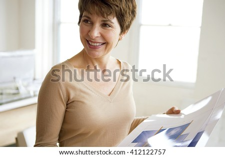 caucasian middle aged woman in office holding project - stock photo