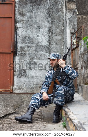 Caucasian military man with black sunglasses in urban warfare sitting with machine gun protecting gate - stock photo