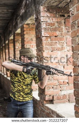 Caucasian military man with black sunglasses indoor urban room space stand with a Kalashnikov rifle near abandoned red brick wall with windows. Corridor in perspective.Empty space for inscription  - stock photo