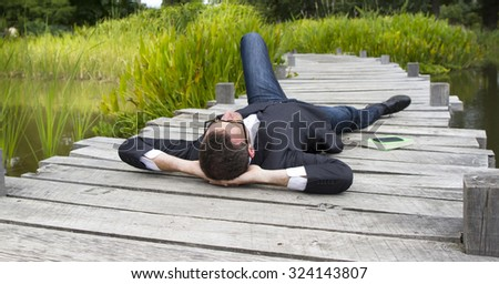 Caucasian modern businessman with hands behind head lying on wood bridge daydreaming and relaxing in city park to think and enjoy lunchtime, back view in daylight - stock photo