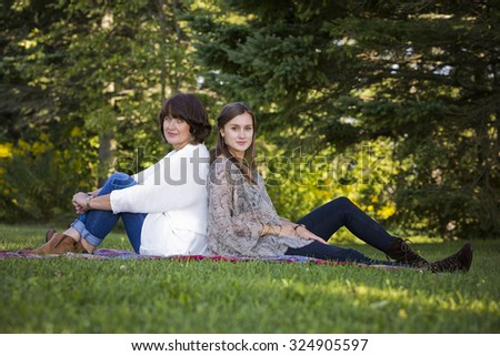 caucasian mother and daughter together in the park - stock photo
