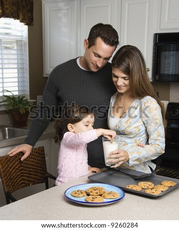 Caucasian mother and father with daughter eating cookies and milk. - stock photo