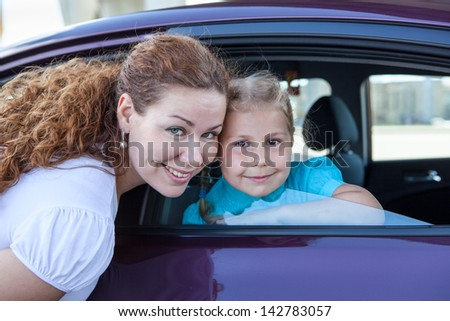 Caucasian mother and little girl together with own land vehicle - stock photo