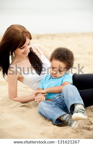 Caucasian mother with a son of an african descend relaxing together outdoors. - stock photo